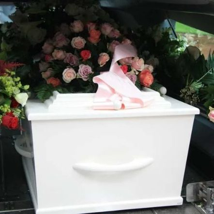 White coffin sitting in the back of a hearse with colourful flowers